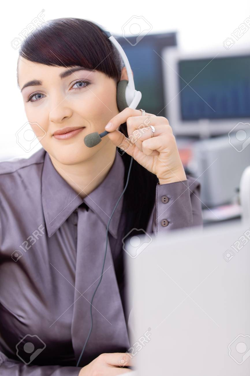 Happy young female customer service operator talking on headset, sitting in front of computer screens, smiling. Stock Photo - 6597216