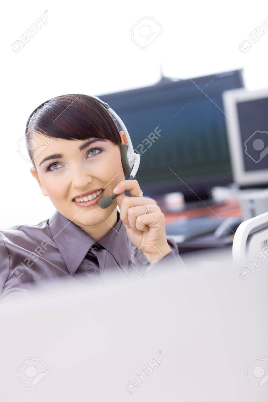 Happy young female customer service operator talking on headset, sitting in front of computer screens, smiling. Stock Photo - 6597248