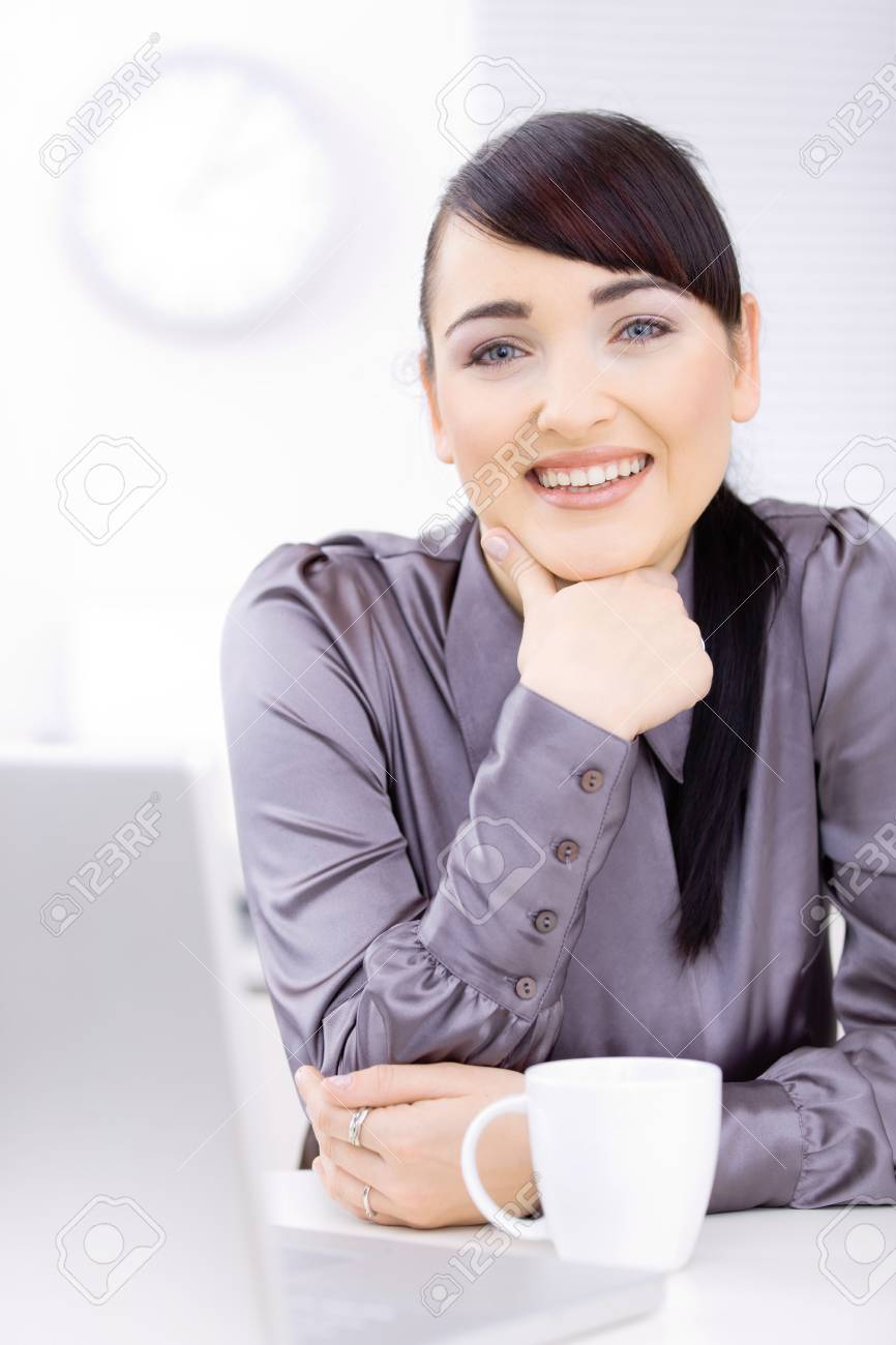 Young businessman sitting at desk at office, thinking, smiling. Stock Photo - 6597230