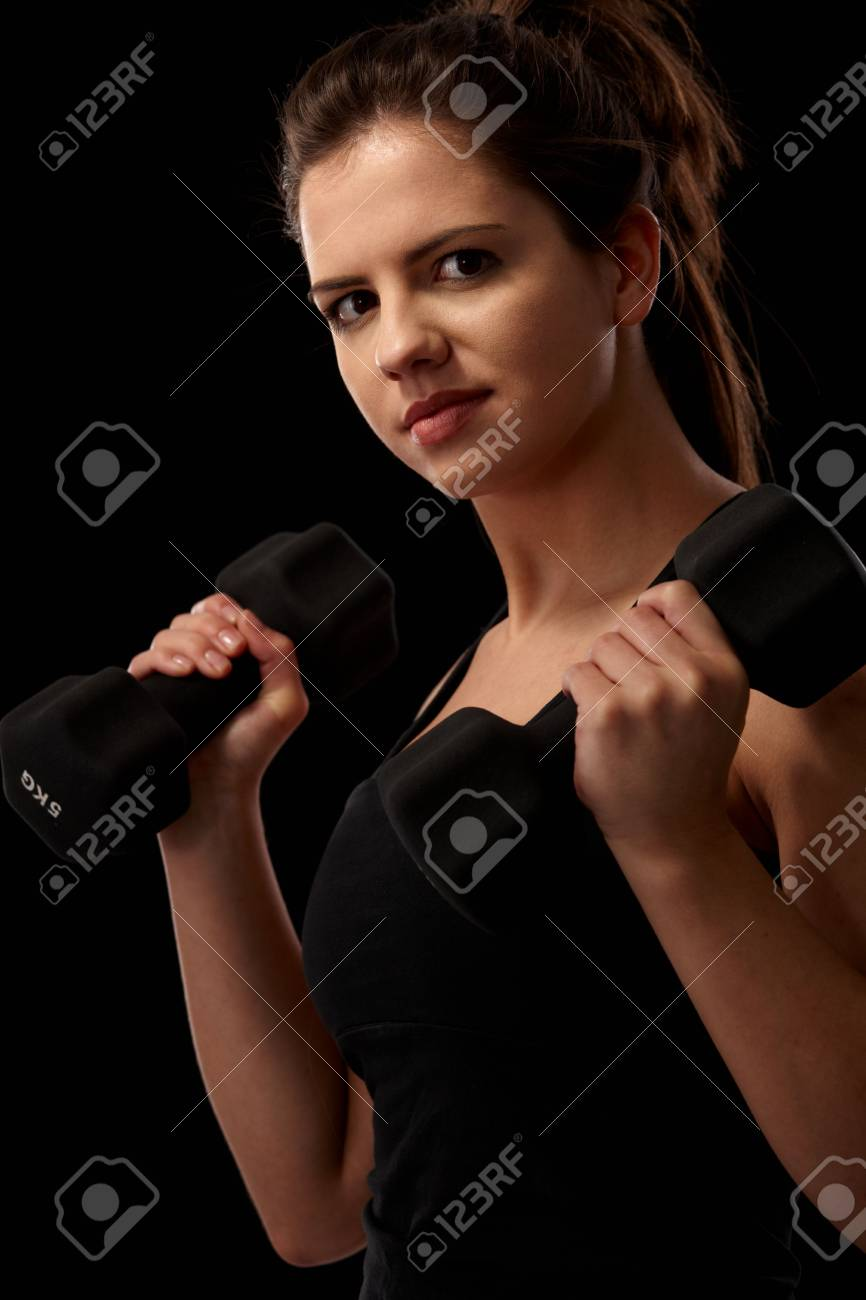 Sporty girl doing exercise with dumbbell looking at camera. Stock Photo - 6711490