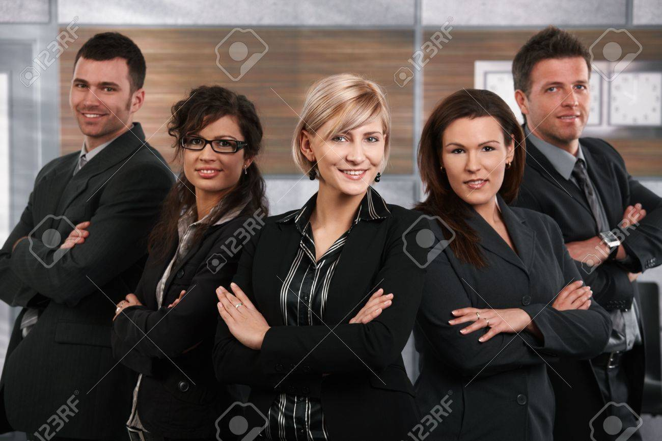 Team of successful happy businesspeople standing in office, businesswoman in front smiling. Stock Photo - 6711560