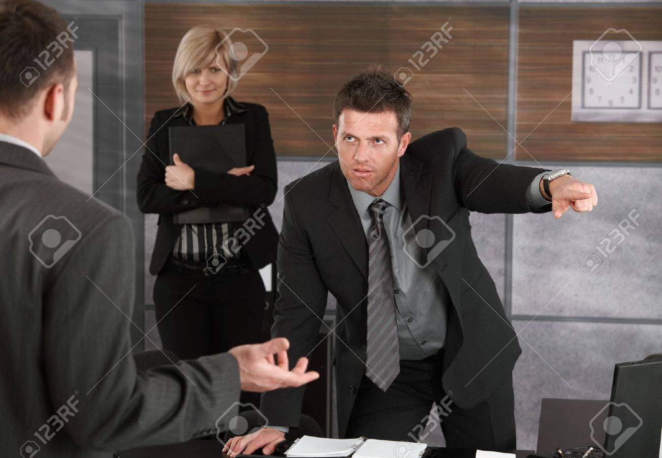 Executive firing employee in office, pointing out of frame. Stock Photo - 6711653