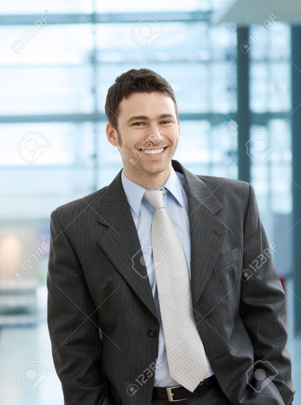 Happy businessman standing with hands in pocket in office lobby, looking at camera, smiling. Stock Photo - 6726331