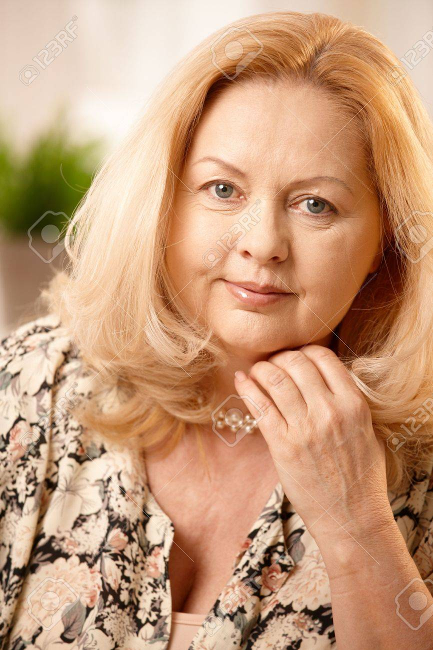 Portrait of mature blonde woman smiling at camera, hand held up to face. Stock Photo - 6746148