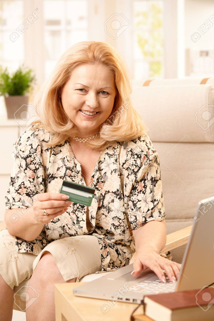 Senior woman smiling at camera while shopping online, holding creditcard and typing on computer keyboard. Stock Photo - 7136685