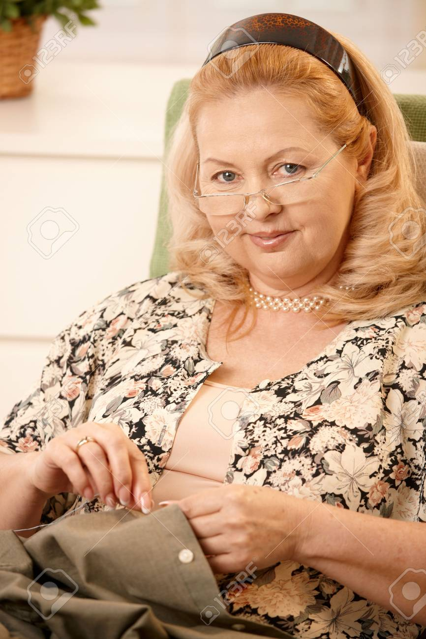 Portrait of mature blonde woman looking at camera, smiling, sewing a shirt at home. Stock Photo - 6746153