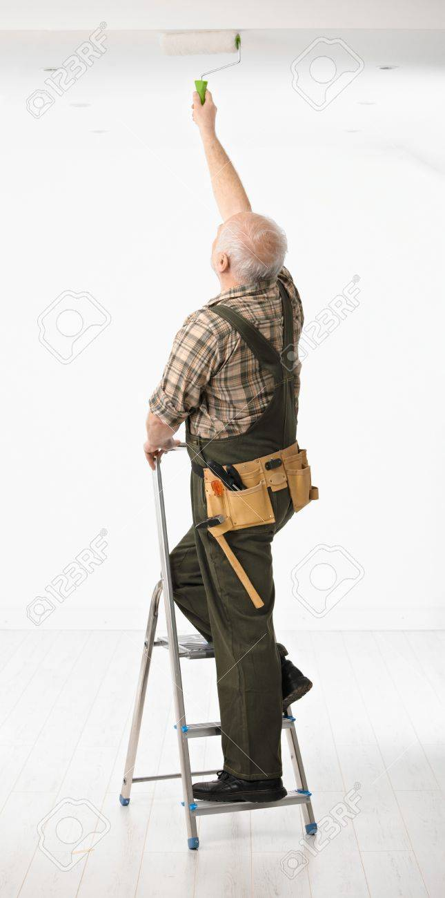 Senior handyman standing on ladder painting the ceiling in white room. Stock Photo - 6927298