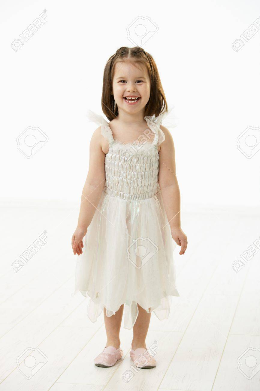 Portrait of happy little girl (4-5 years) wearing ballet costume looking at camera, smiling. Studio shot over white background. Stock Photo - 6927331
