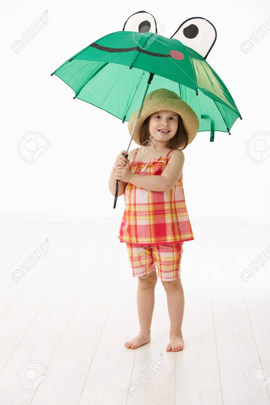 Happy little girl (4-5 years) in summer dress and straw holding umbrella over white background. Stock Photo - 6927333