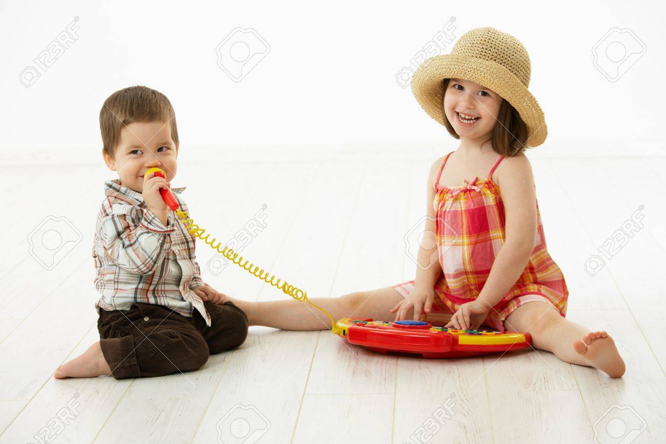Happy kids playing on toy music instrument, little boy singing to microphone over white background. Stock Photo - 6927287