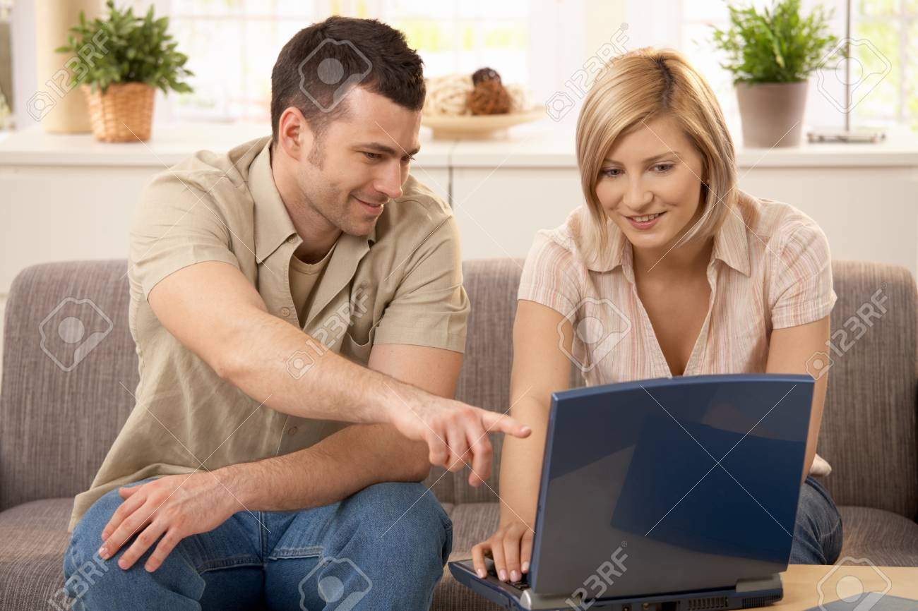 Young man pointing at laptop computer screen, pretty girlfriend smiling. Stock Photo - 7016107