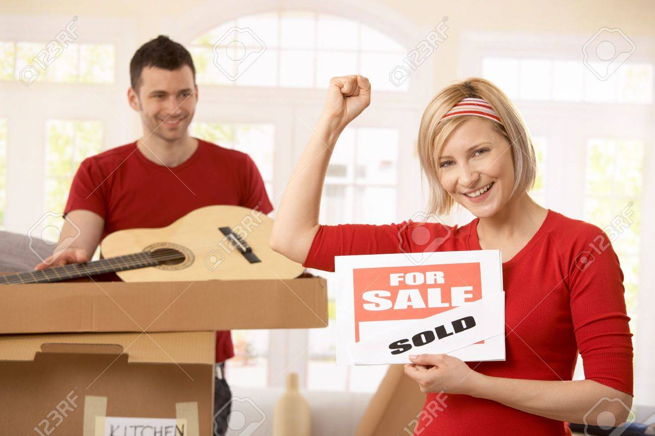 Smiling woman holding sold sign raising fist, happy man looking at her in background, unpacking boxes. Stock Photo - 7015745