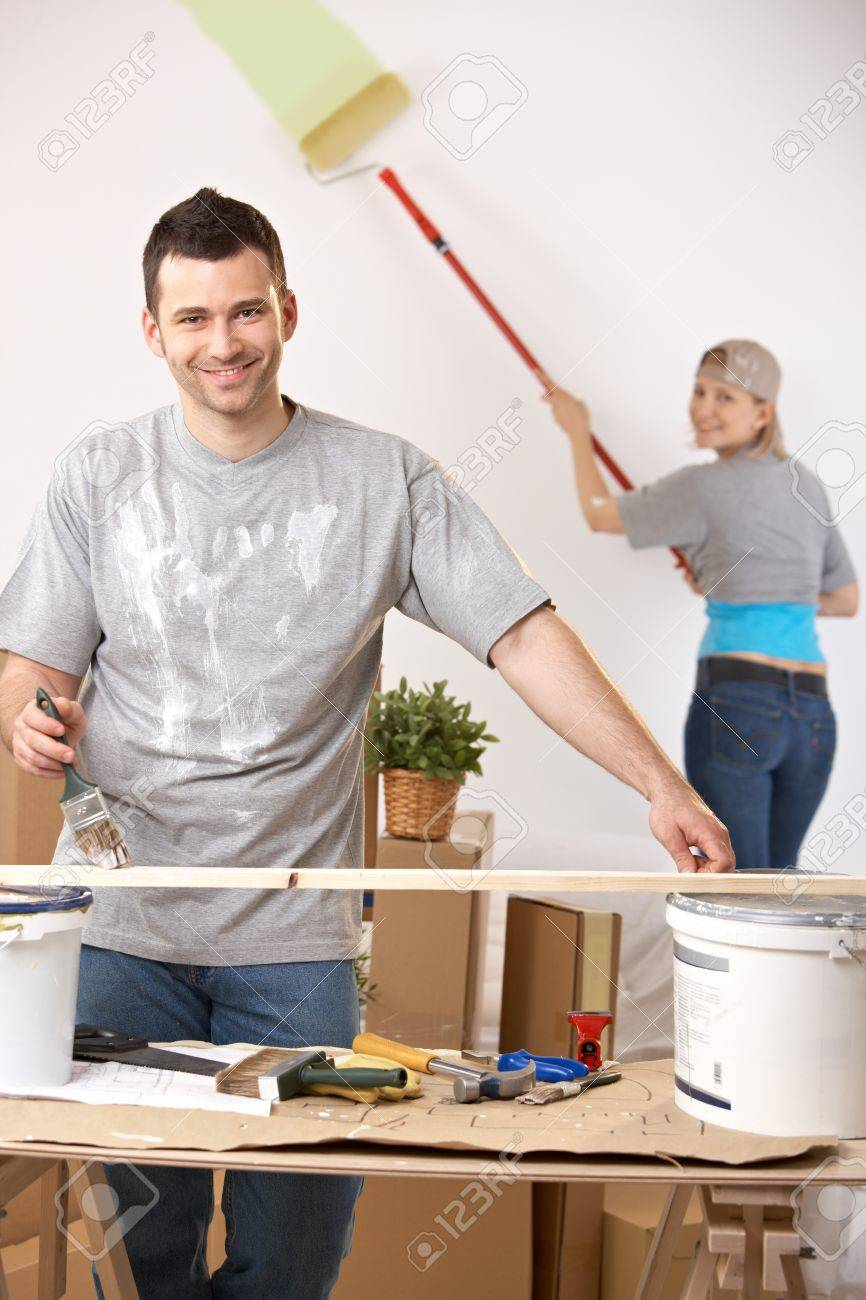 Cheerful young man painting stave at table, girlfriend painting wall in background. Stock Photo - 7016101