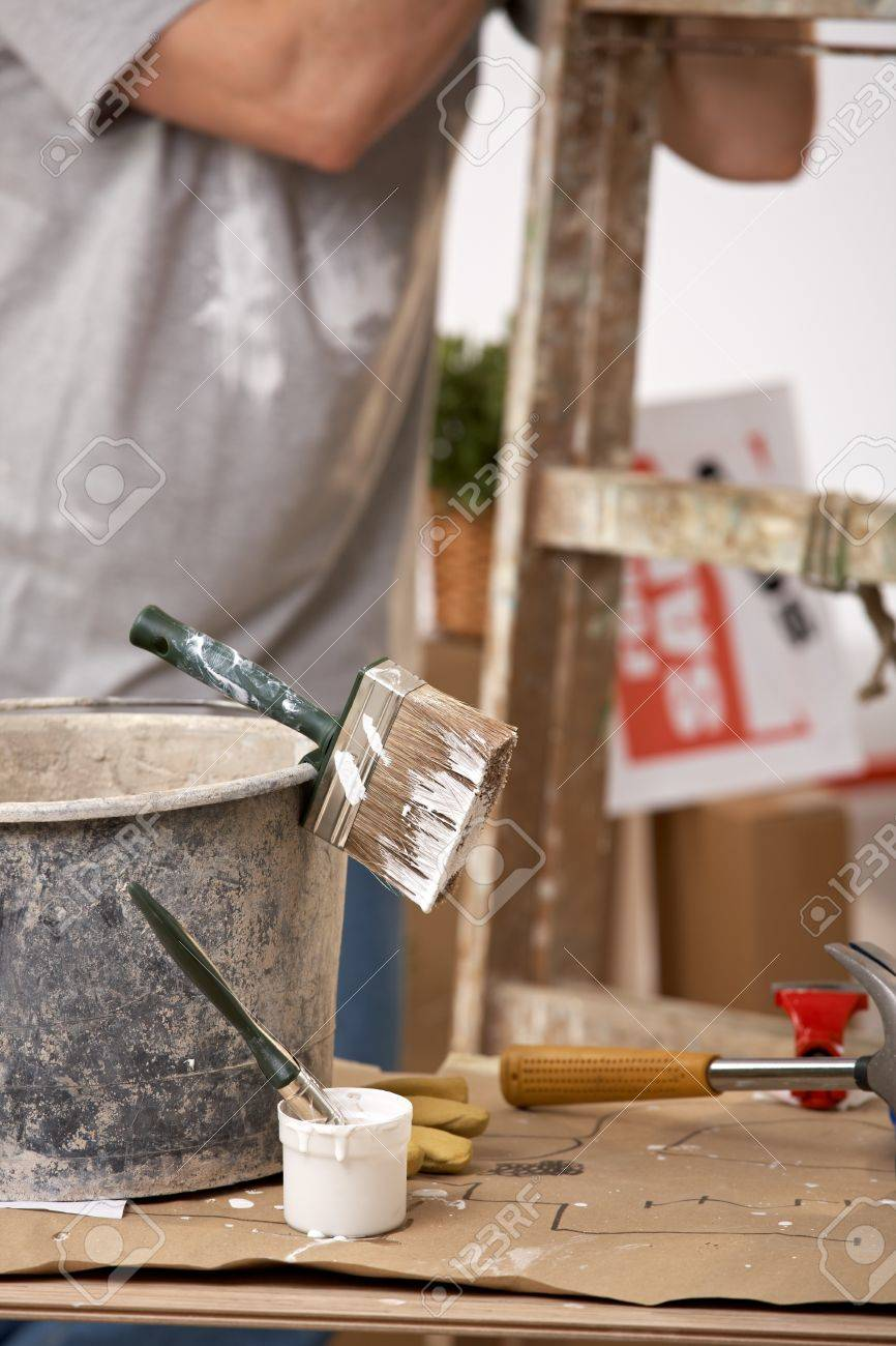 Focus on painting equipment, brush and bucket, man standing by ladder in background. Stock Photo - 7011076