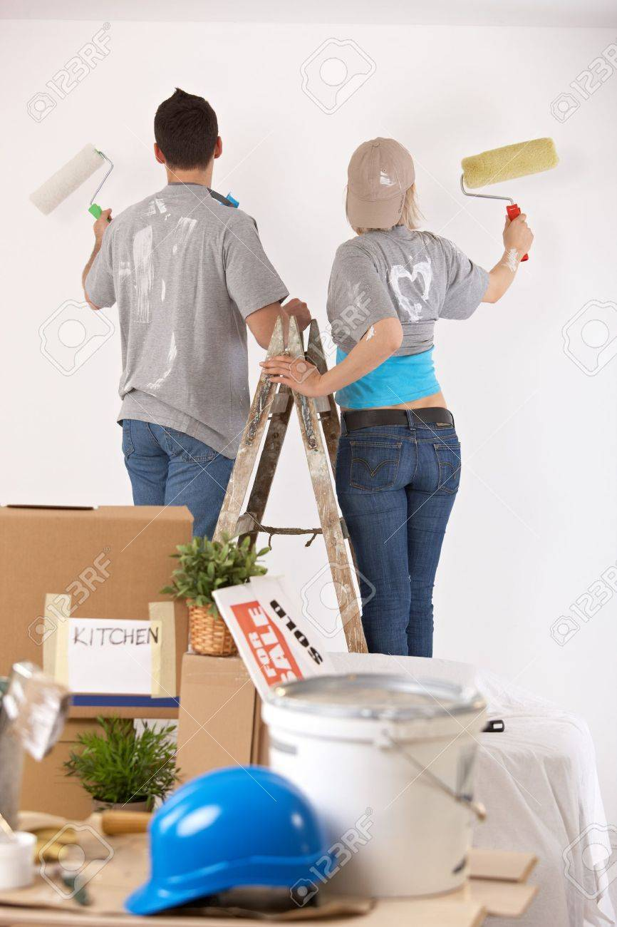 Couple Standing On One Ladder Painting Wall Together With Paint Roller Stock Photo