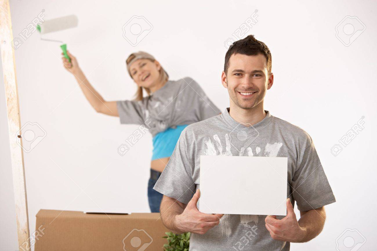 Happy couple painting new house together, smiling man holding blank page for copyspace. Stock Photo - 7003264