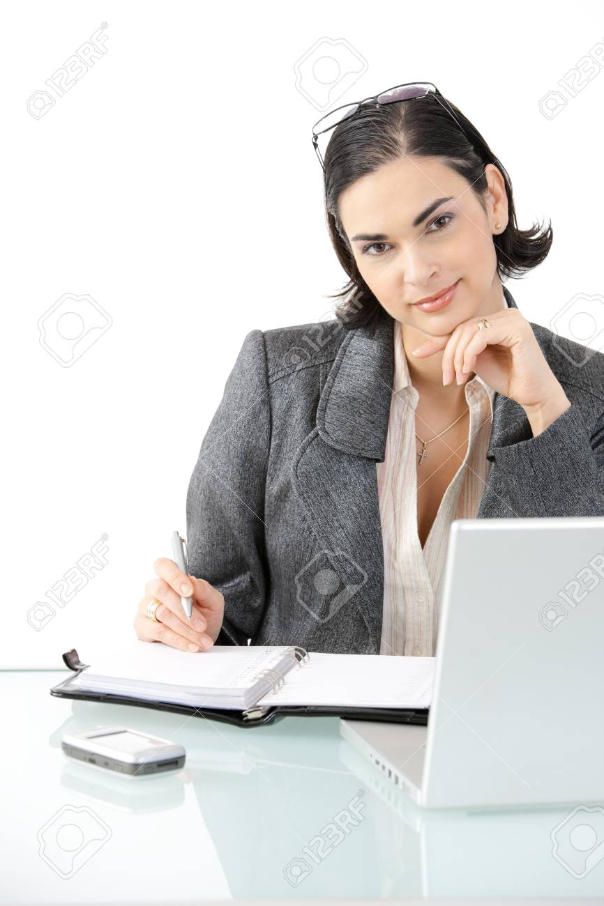 Young businesswoman sitting at office desk with laptop computer and organizer, looking at camera, smiling. Isolated on white background. Stock Photo - 7016271