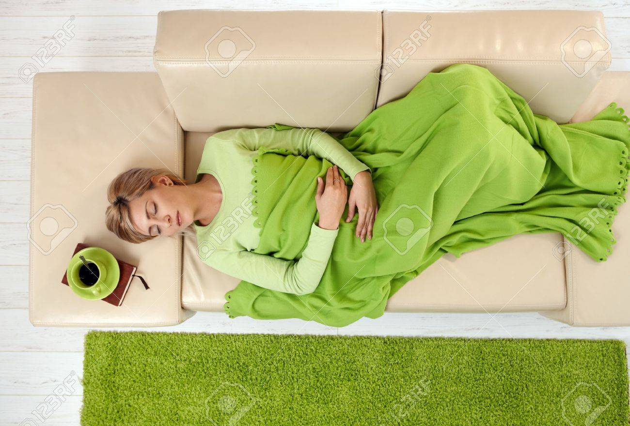 Sleeping woman in high angle view lying on sofa under blanket. Stock Photo - 7016345
