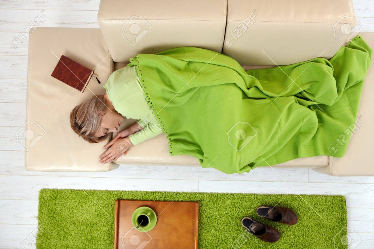 Sleeping woman in high angle view lying on sofa under blanket. Stock Photo - 7016372