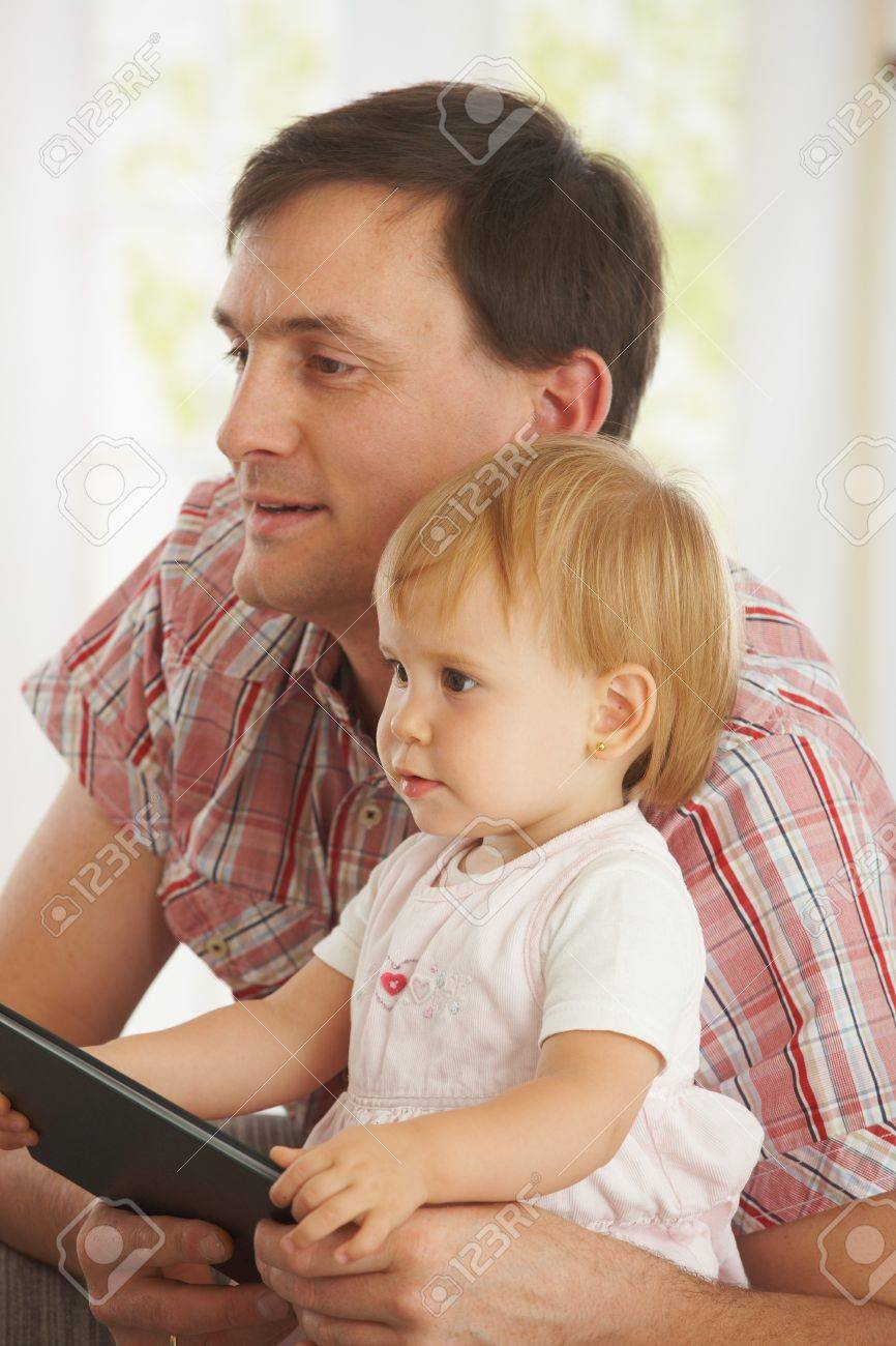 Father cuddling little daughter (1-2 years toddler) at home, smiling. Stock Photo - 7058863