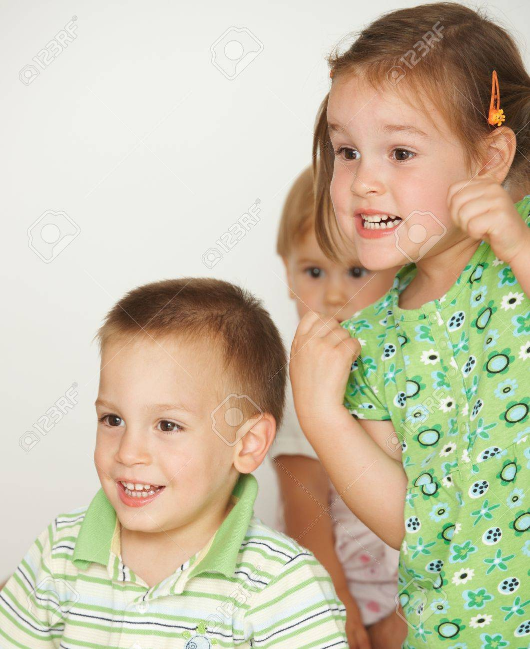 Happy little children at attention, white background. Copy space in top left corner. - 7058775