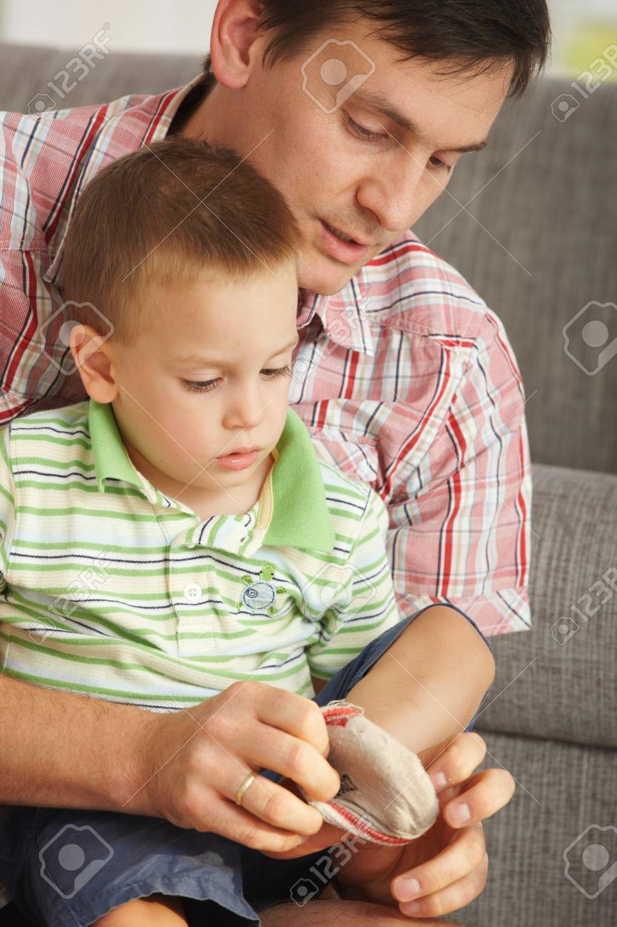 Father helping son putting on socks at home. Stock Photo - 7058882