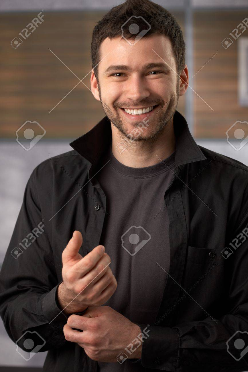 Happy trendy man posing in black shirt doing the button. Stock Photo - 7082792