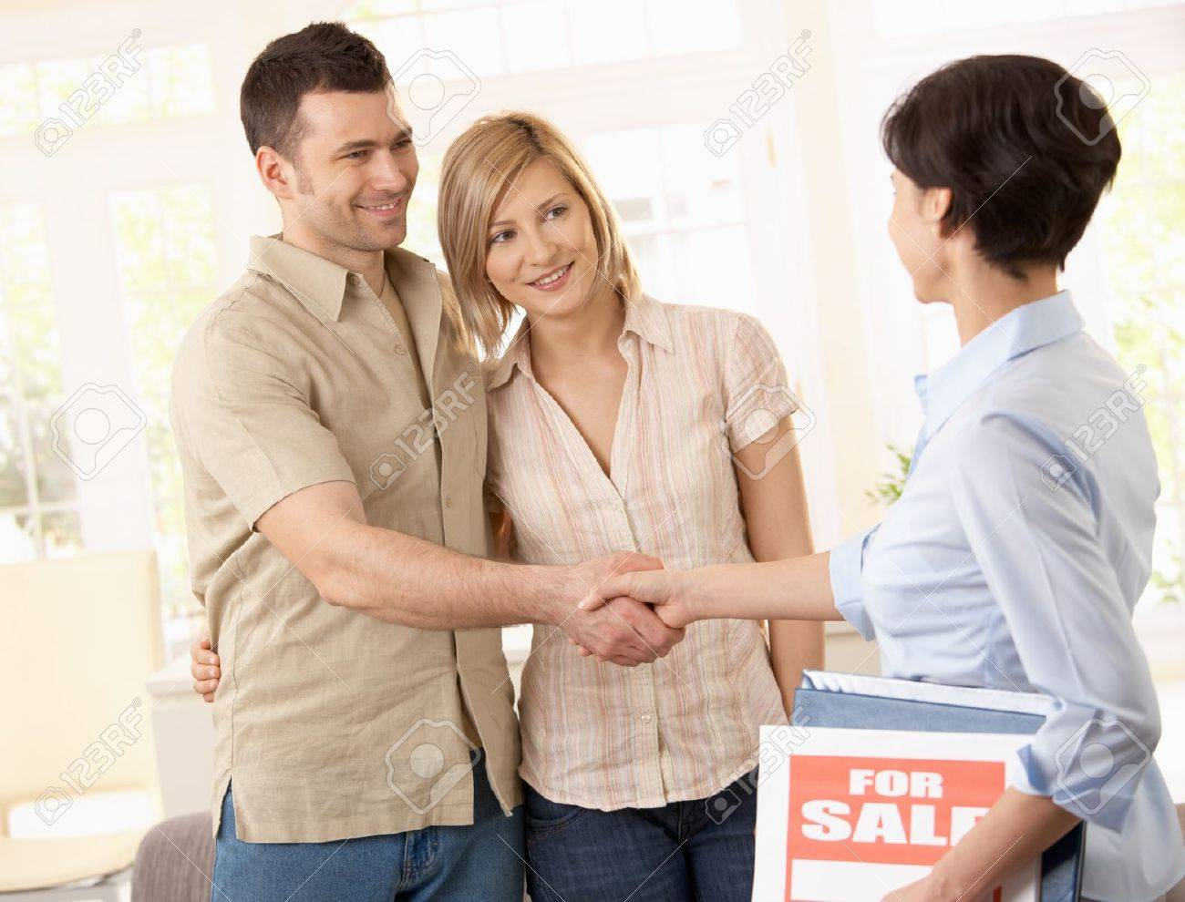 Estate agent congratulating young couple on making deal on new house. Stock Photo - 7217276