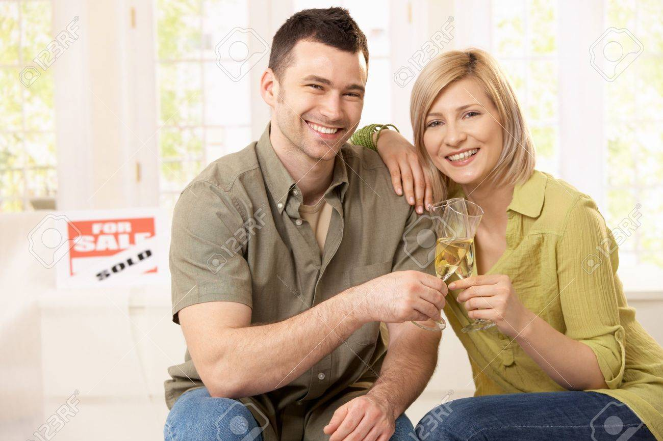 Portrait of happy couple celebrating purchase of new home, laughing at camera. Stock Photo - 7217342