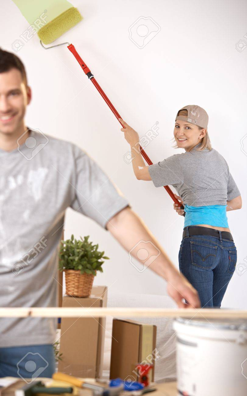 Smiling young woman in focus painting wall with paint roller, man working at table. Stock Photo - 7217273