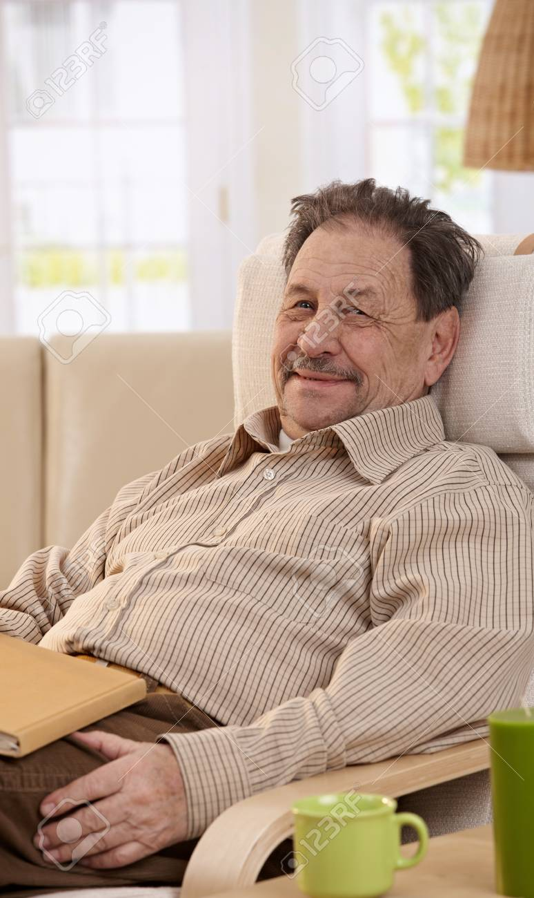 Senior man resting in chair at home, reading book. Looking at camera, smiling. Stock Photo - 7249279