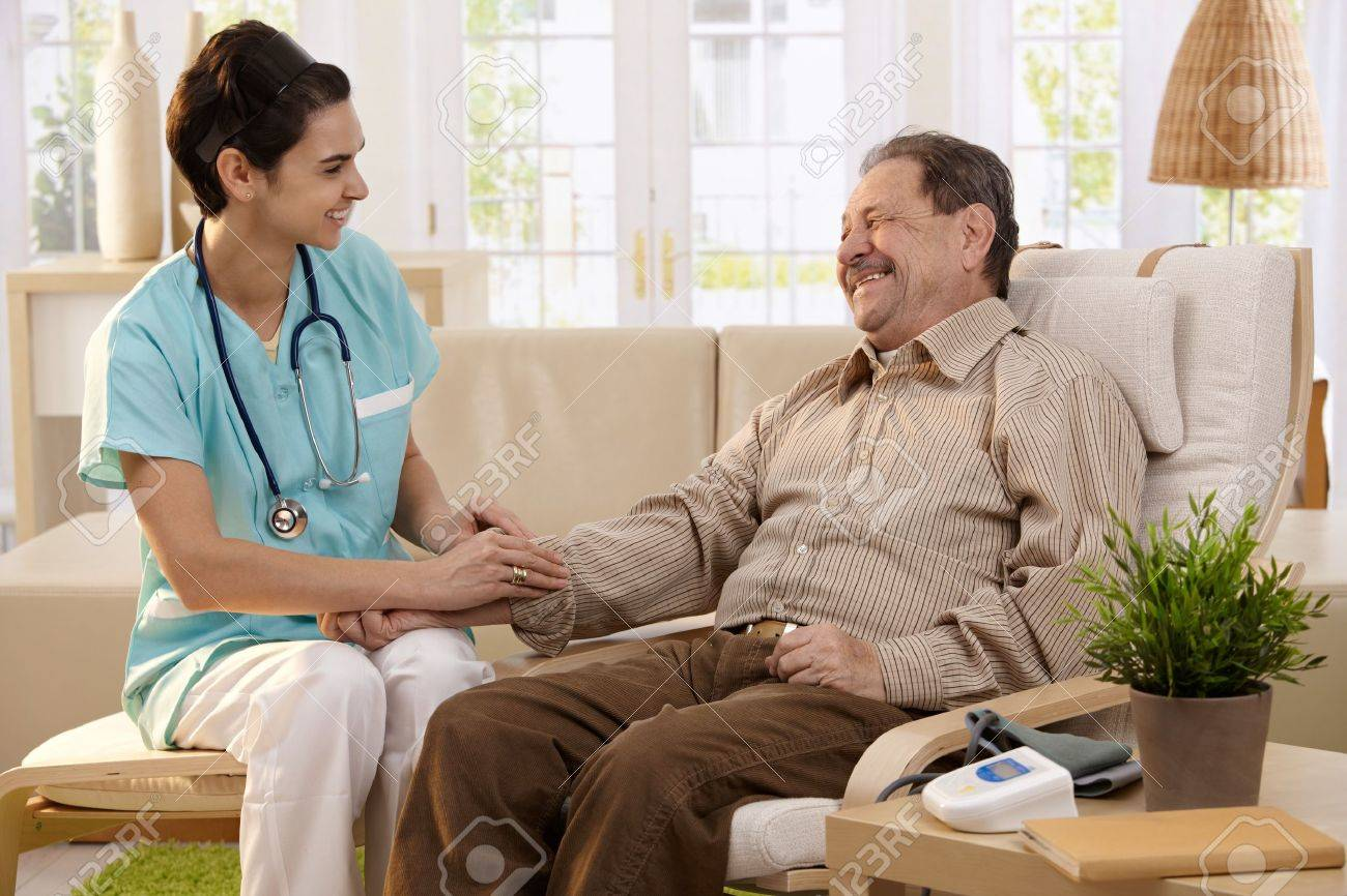 Nurse measuring blood pressure of senior man at home. Smiling to each other. Stock Photo - 7249305