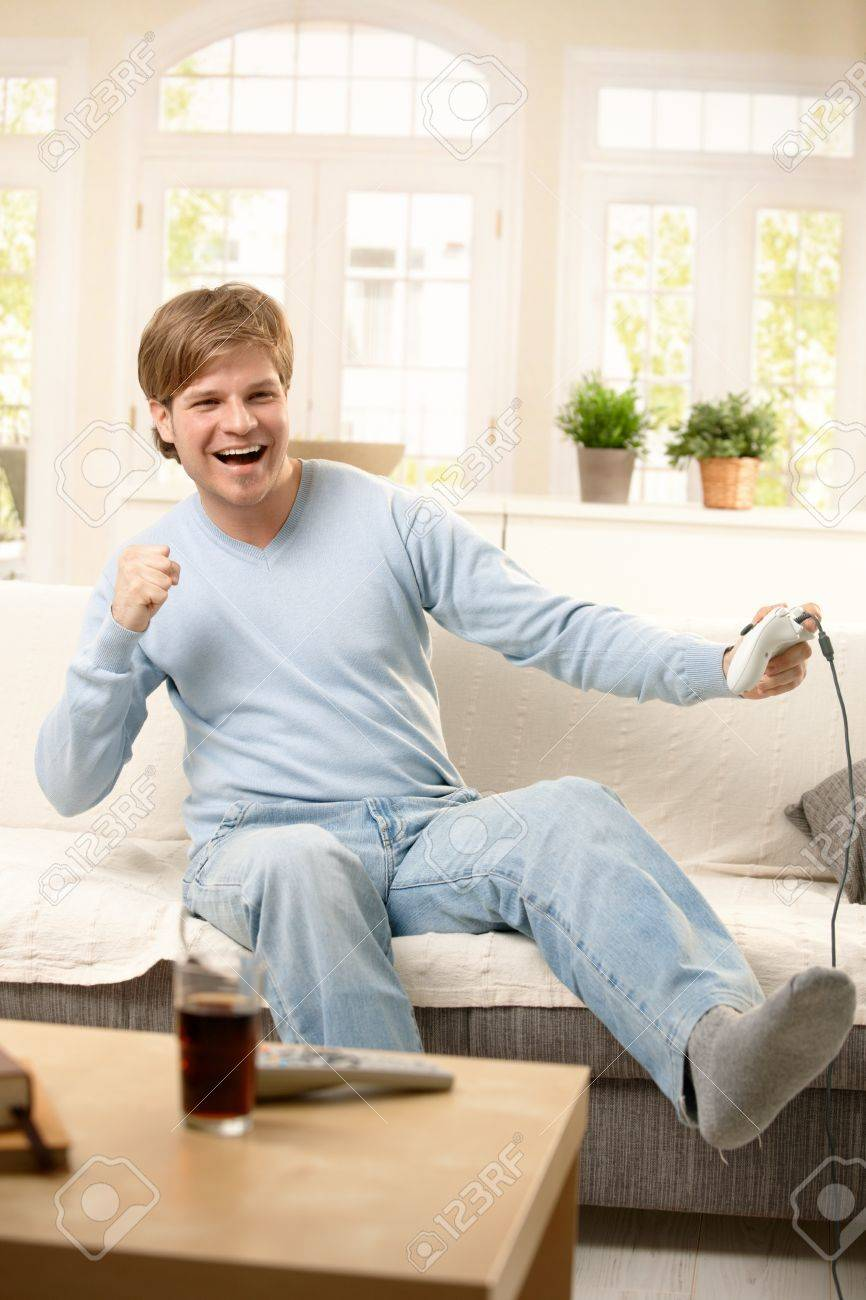 Happy Guy Playing Computer Game At Home, Sitting On Living Room ...
