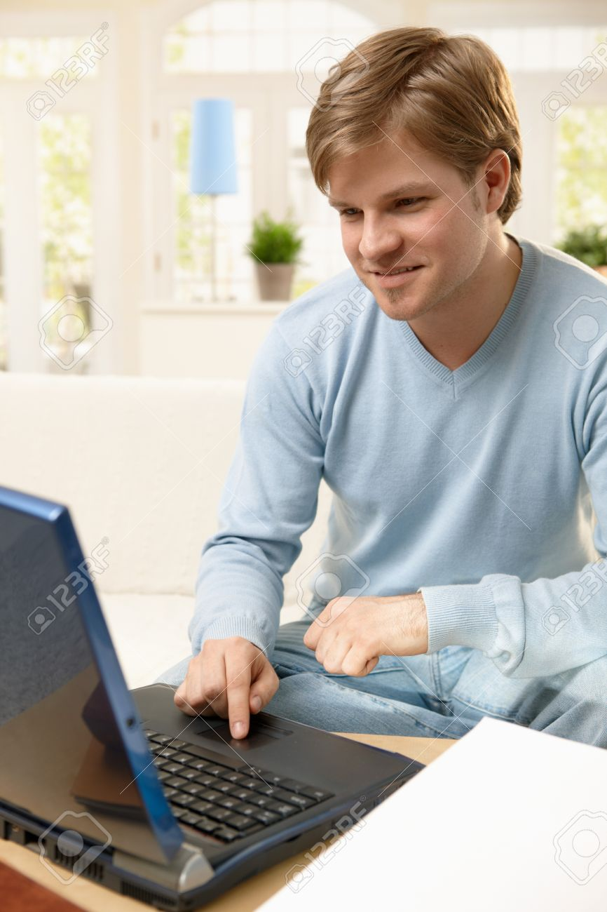 Goodlooking guy using laptop computer, browsing internet at home, smiling. Stock Photo - 7249338