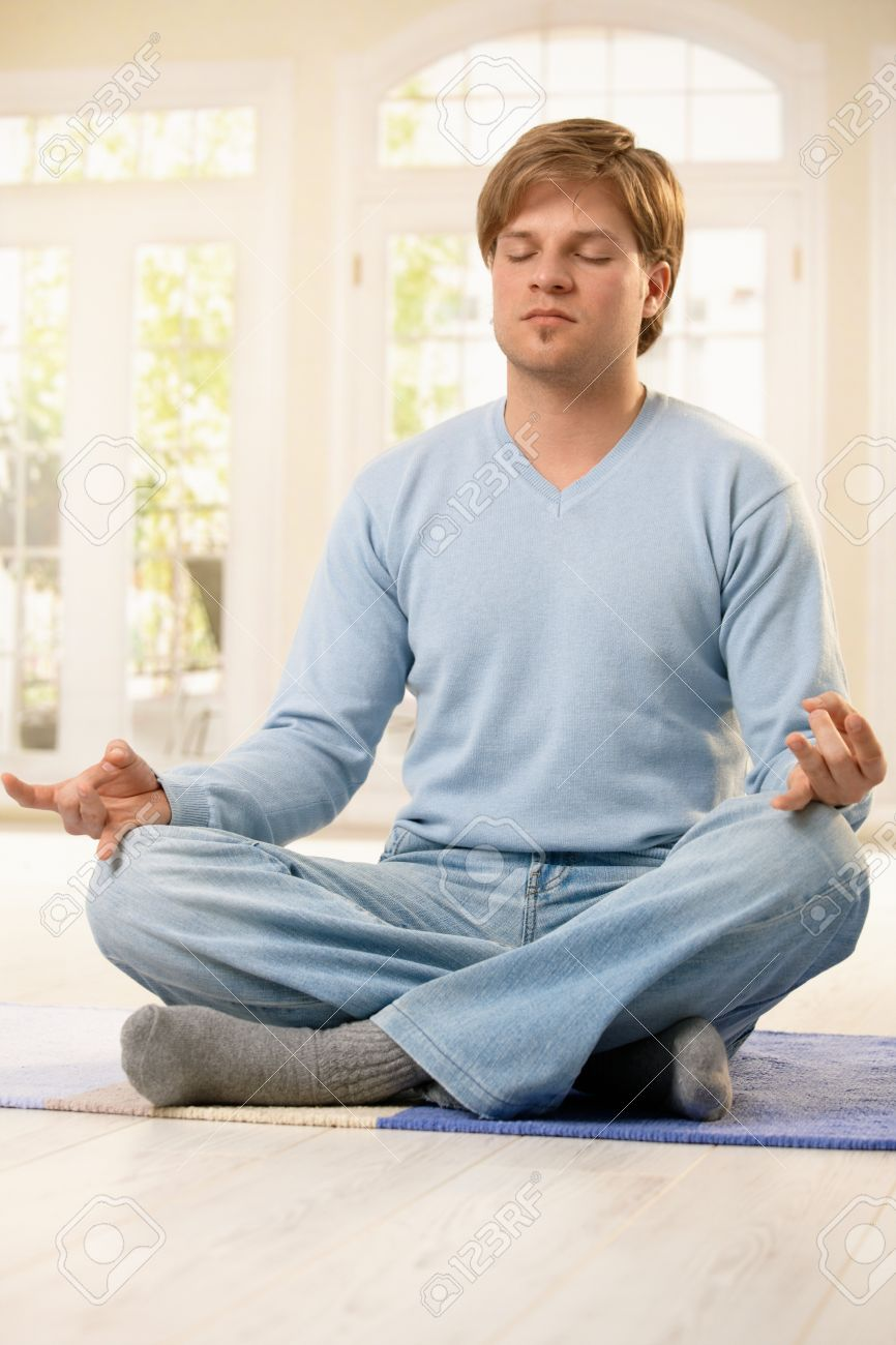 Man sitting on living room floor in lotus posture, doing yoga meditation exercise with closed eyes. Stock Photo - 7249297