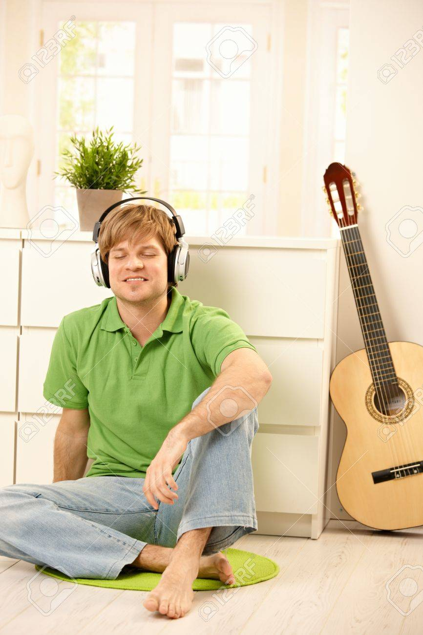 Goodlooking guy sitting on bright living room floor next to guitar, listening to music via headphones, smiling with closed eyes. Stock Photo - 7249380
