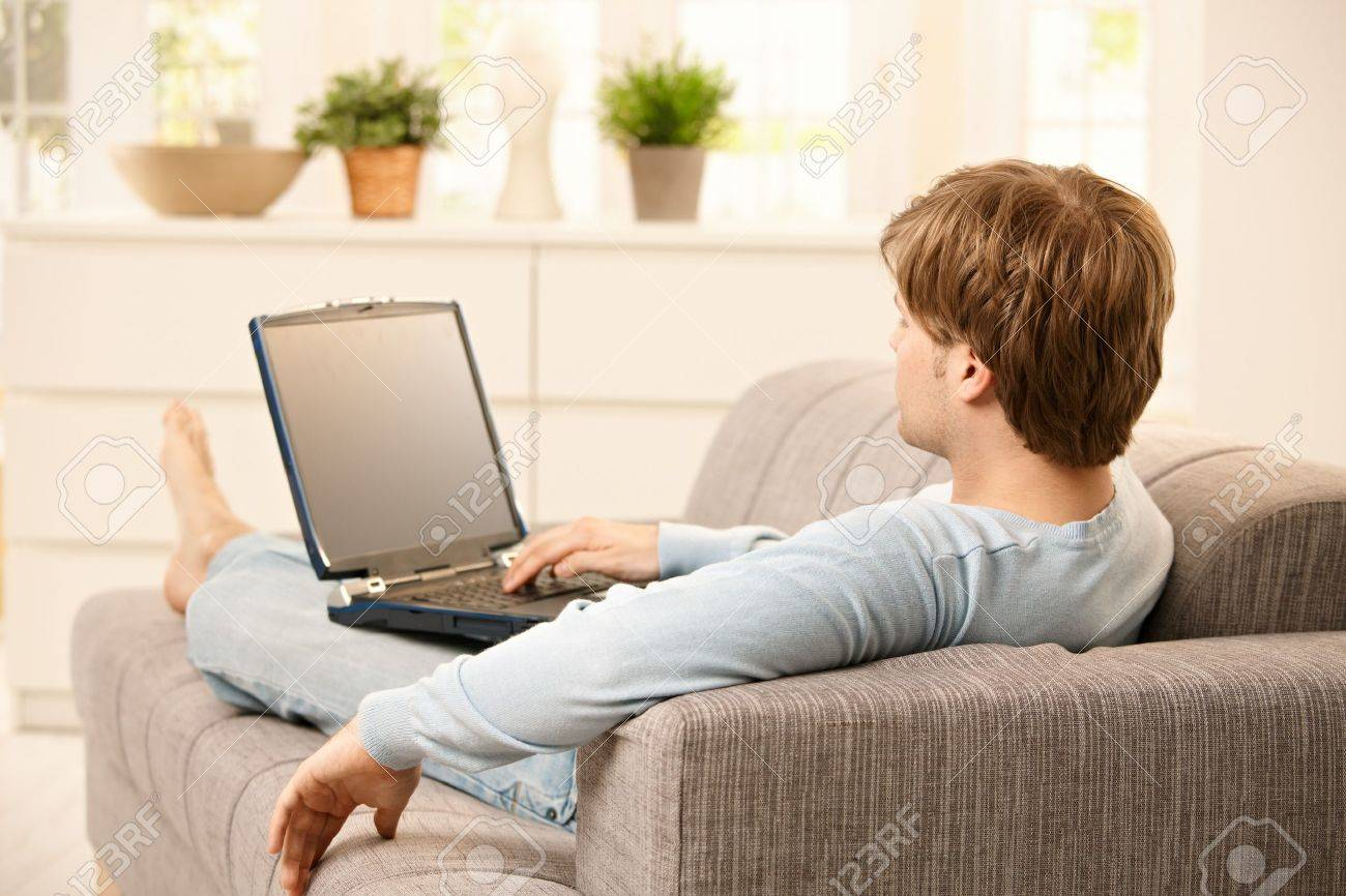 Man Living Room Man Using Laptop Computer Sitting On Couch In Living Room Stock