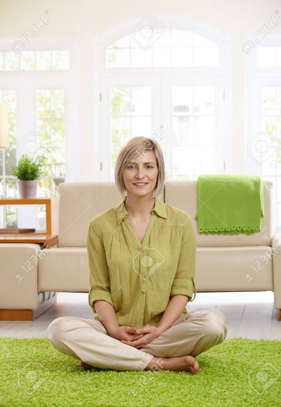 Happy  woman sitting with legs crossed on living room floor, looking at camera. Stock Photo - 7257516
