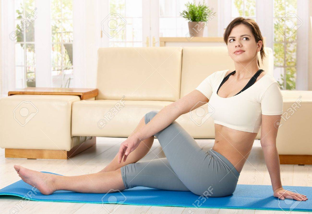 Girl Doing Exercise On Polyfoam Mat In Living Room Stock Photo