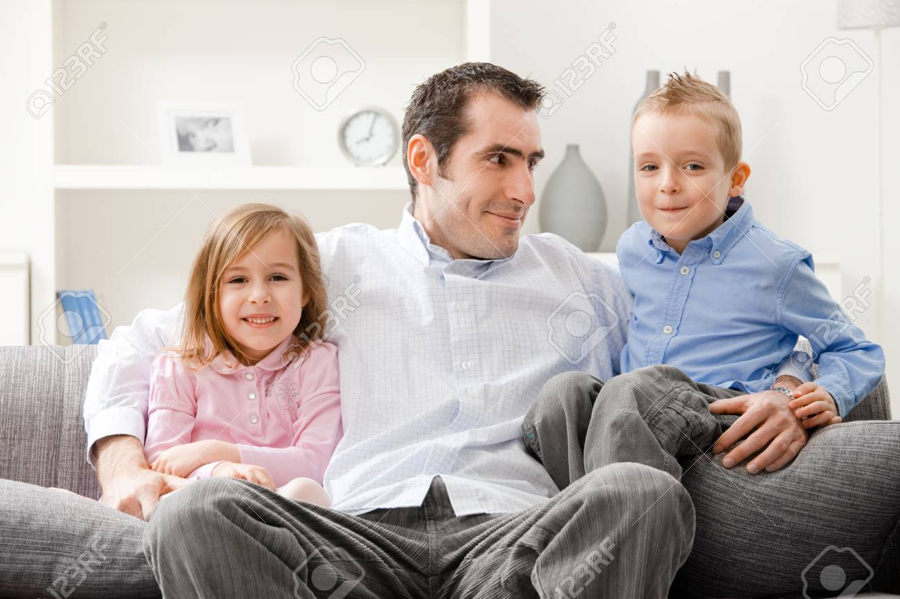 Happy family, father and siblings sitting together on couch, smiling. Stock Photo - 7273394