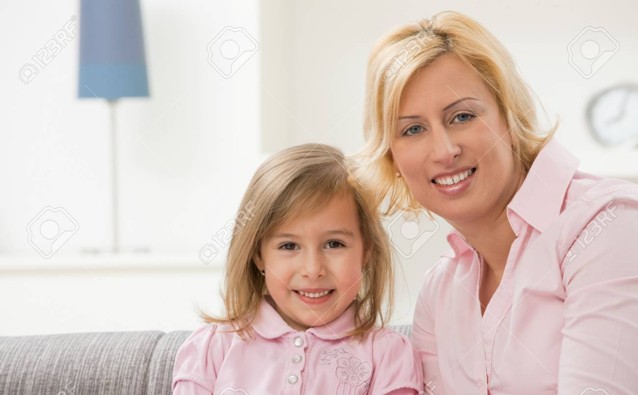 Portrait of blonde little girl and mother wearing pink, smiling. Stock Photo - 7271553