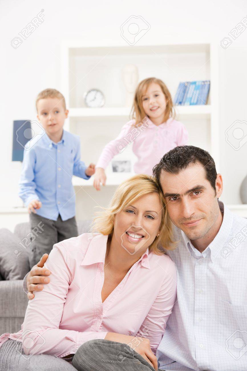 Happy couple sitting at floor at home, embracing. Their children jumping on couch in background. Stock Photo - 7271560