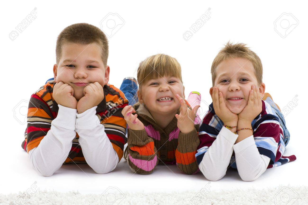 Group of 3 happy children lying on floor, wearing  colorful, striped pullover and t-shirt, laughing.  Isolated on white background. Stock Photo - 7284171