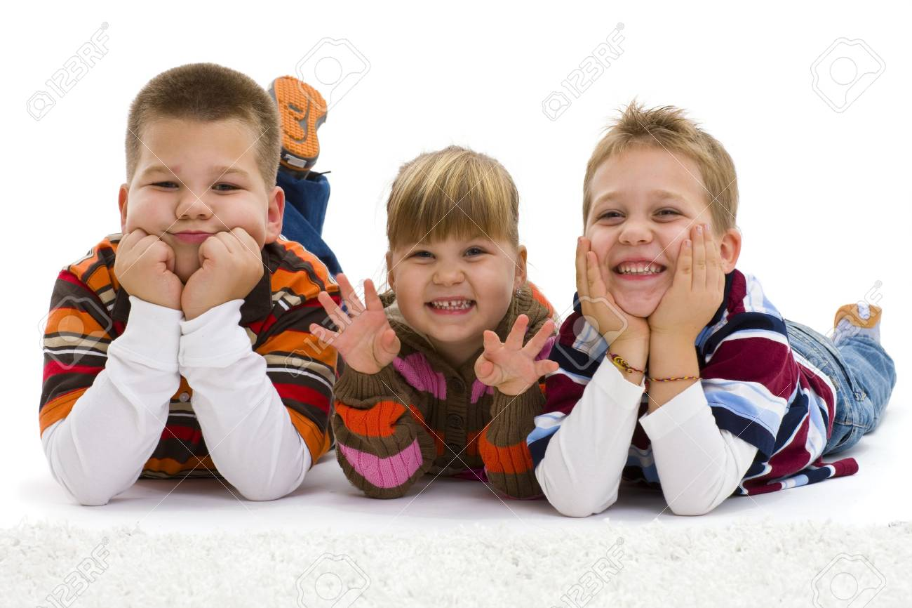 Group of 3 happy children lying on floor, wearing  colorful, striped pullover and t-shirt, laughing.  Isolated on white background. Stock Photo - 7284173