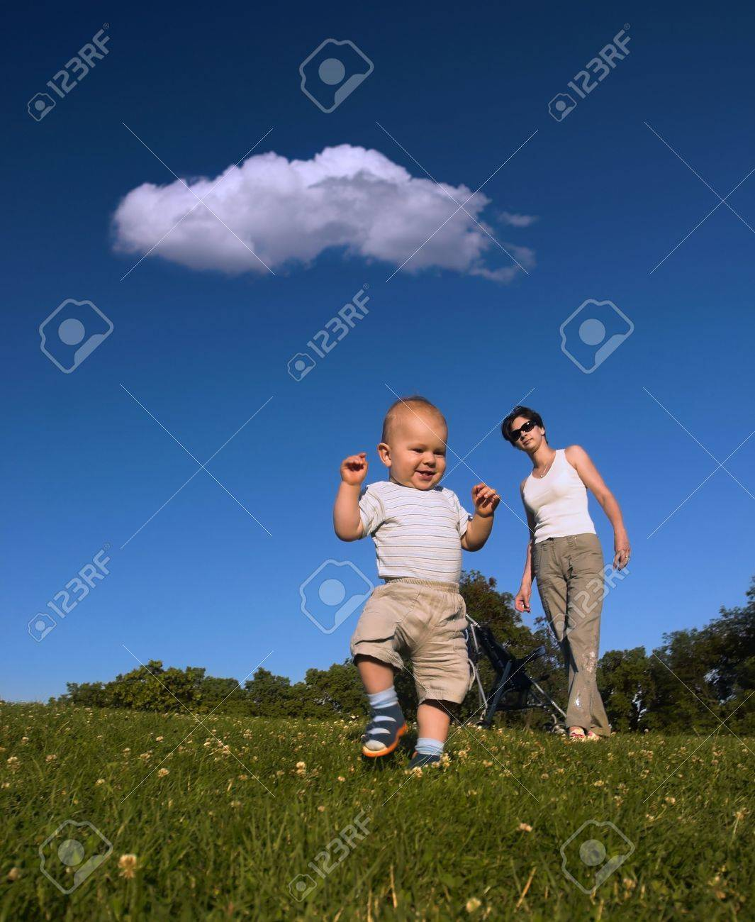 10 months old baby is doing his fist little steps while his mother is watching him. Stock Photo - 7283652