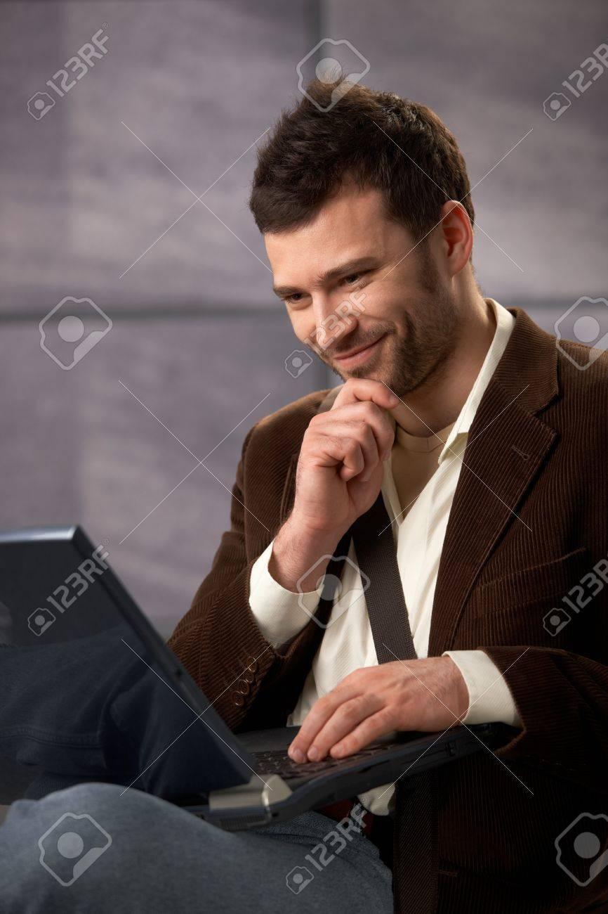 Happy guy wearing stylish clothes using laptop computer, smiling. Stock Photo - 7347764