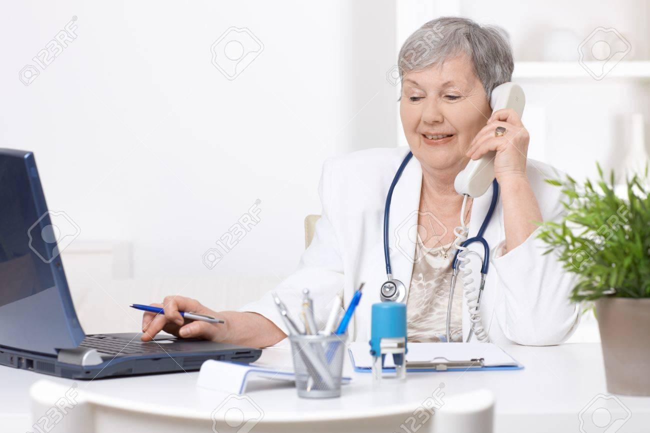 Senior female doctor, working at desk, using laptop computer. Stock Photo - 7347656
