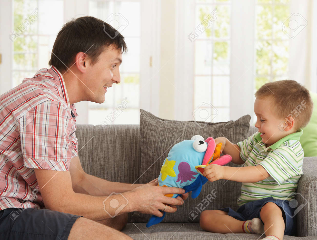 Happy father and son having fun playing on couch at home. Stock Photo - 7434940