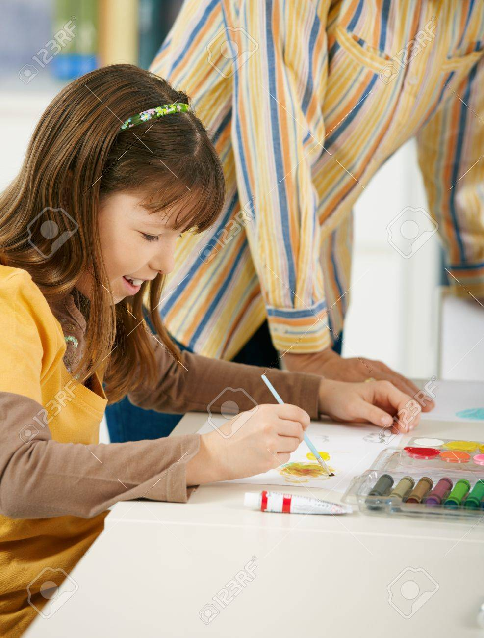 Elementary age girl sitting at desk enjoying painting with colors in art class at primary school classroom, smiling. Stock Photo - 7434859