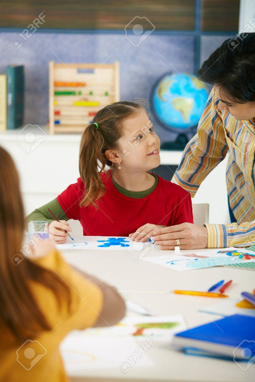 Teacher teaching painting to elementary age children in classroom at primary school. Stock Photo - 7434877